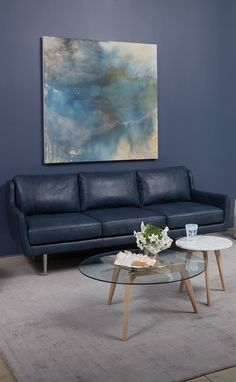 A blue leather sofa is a great way to make a stylish statement. Neutralize this bold decor choice with simple furnishings in non-distracting materials like glass and marble.