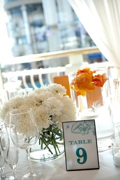 Centerpieces were created with white football mums, and masses of white carnations. Orange roses and petals were used floating in cylinders of water