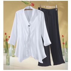 """Gauze Tunic  Free Flowing Gauze Tunic and Cropped Pants. The easiest of styles in breezy gauze. White V-neck tunic has a front ruffle, angled tucks, 3/4 sleeves, and a four-point, handkerchief hem. Hidden button front is accented with one decorative button at the top. Misses' 32"""" long, Women's 35"""" long. Black cropped pants have a cotton voile lining, drawstring elastic waist, flat front inset, and side pockets. Women's 28"""" inseam. Both are 100% crinkle cotton gauze."""