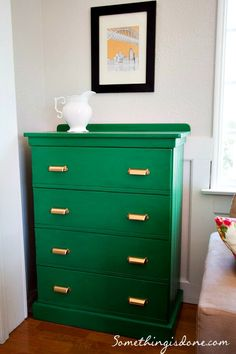 Emerald green dresser with Behr Paint and Primer in Pine Grove and brass pulls by Martha Steward (http://somethingisdone.com/painted-emerald-living-room-dresser/)