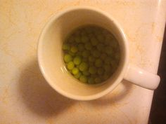 3 First thing, throw frozen green peas with water in a cup to thaw.