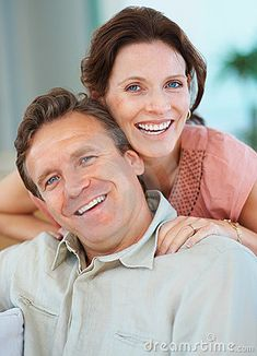 Smiling middle aged couple relaxing at home by Yuri Arcurs, via Dreamstime