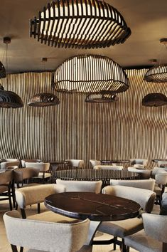Designed in an effervescently refreshing fashion by Innarch, the Don Café House in Pristina, Kosovo offers a hangout that is unique and energizing. The walls of the café are shaped to mimic the curves of a giant sack containing coffee beans inside. Both the color and the contours of the large wall made up of wood help accentuate this affect, while the decor and the furnishings play their part to perfection.