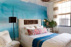 azure blue wall, with watercolor-like effect, and pale smudges of pink paint, bedroom wall decor, inside a room with white bed, with decorative headboard and colorful bedding