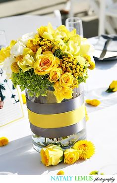An arrangement of yellow flowers in a clear vase accented with gray and yellow is the perfect wedding centerpiece.