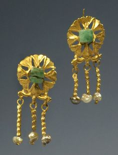 PAIR OF OPENWORK ROMAN GOLD, EMERALD, AND PEARL EAR PENDANTS  The openwork disc of lotus flowers with a central emerald bead on a cross-wire, with three pendants hanging from a scrolled crossbar below, each pendant a hollow ribbed tube threaded with small seed pearls.  Ca. 3rd Century AD  L. 11/4 in. (3.3 cm.)  Ex private English collection, acquired in the 1980s in London.  Published: J. Eisenberg, Art of the Ancient World, 2007, no. 174.