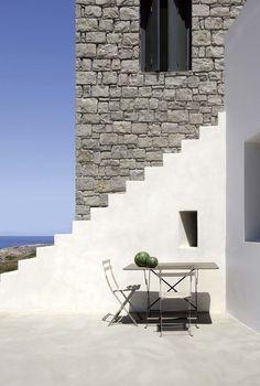 Passage secret. Contraste entre les murs en appareillage de pierres locales et les marches immaculées. L'île de Milos pointe ses côtes dentelées au sud des Cyclades.