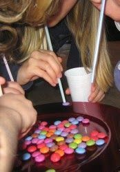 Suck up as many M&Ms with a straw as you can in 60 seconds.   Blue Zone: Party games to rock your partaaay!
