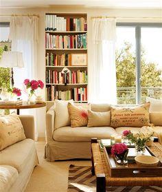 Salón en tonos tierra con librería entre ventanales
