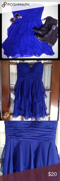 Strapless Ruffled Minidress This vibrant blue dress features flirty ruffles and a padded bodice with boning in the sides for support. There is a thin rubber strip along the top inside which keeps it in place all night. It zips in the back. Arden B Dresses Mini