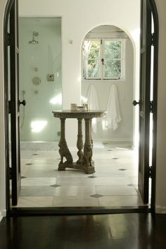 Nate Berkus - beautiful bath with carrara marble floor, arched doorway, and antique center table