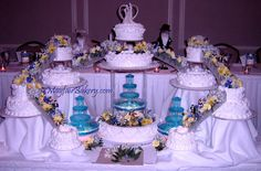 "Megan - 40 to 50 lbs. Serves 200 to 250+. Center cake 7"" top tier, 12"" middle, clear crystal fountain set on a 20"" base tier. Side cakes = 6-6"" / 2-9"" / 2-10"" with 6 clear stairs. This one of a kind cake was designed for a relative and required 3 people working for 90 minutes to assemble and decorate with flowers. MayfairBakery.com"
