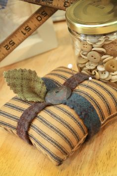 <3 - this is so simple and so sweet..ticking pillow, felt strips, and old button and a felt leaf...