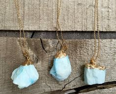 A bright baby blue raw tourmaline stone has been gold electroplated and hangs from a gold plated chain. The raw tourmaline has varying hues of blues and whites with a little sparkle coming from...@ artfire