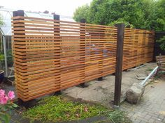 Slatted cedar privacy screen.  Horizontal with orangey stain, maybe with a little bit wider boards, but enough of a gap to peek through.