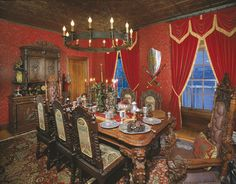 This is a beautiful example of a cozy medieval dining room.  Grand chandelier, carved detailing, and plush draperies - love it!