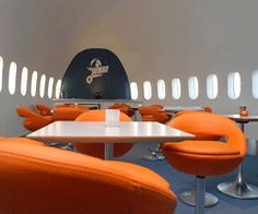 meeting room in redesigned old aircraft decorated with orange furniture