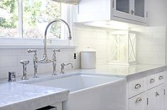 Galley kitchen's farmer's sink with Perrin & Rowe Bridge faucet, white glass-front cabinets and marble counter-tops | Titan and Co