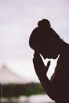 silhouette of peaceful woman in prayer position by alexgrabchilev | Stocksy United