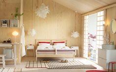 Keskikokoinen makuuhuone, jossa parisänky käsittelemättömästä männystä sekä valkoiset yöpöydät ja puna-valkoiset petivaatteet.