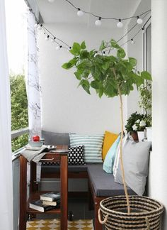 kleinen Balkon gestalten Lichterkette Wurfkissen grüne Pflanzen bunter Bodenbelag