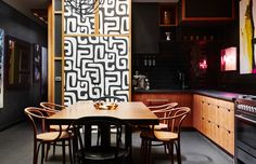 mudcloth print translated into a modern wallpaper in this black moody and edgy kitchen. love the neon art.