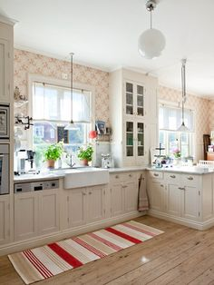 Love this cottage kitchen with the red and white wallpaper and ever popular striped rug/pale hardwood floors.Nothing BUT WONDERFUL things to say about this Kitchen. Cozy Kitchen, Country Kitchen, Kitchen Decor, Kitchen Design, Red Kitchen, Kitchen Rug, Kitchen Walls, Nice Kitchen, Kitchen Layout