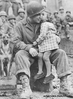 US Army Signal Corp Photo Tec-4 Elvin Harley getting a kiss from a French child while listening to the US 9th Armored Division Band near Aboncourt, France, 14 Feb 1945 / L. G. Crabtree