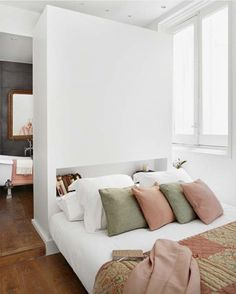 Madrid pastel apartment with headboard as room divider between bedroom and bathroom