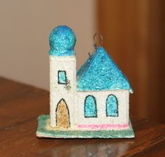 Miniature Blue Domed Czechoslovakian Greek Orthodox Chapel. Cardboard Ornament. 1930s.  These were created in Czechoslovakia, and their story is most interesting. Krebs & Son, the original European business was founded by grandmother Erika Krebs, who was trained in the ornament business as a child in German Bohemia and Czechoslovakia. After World War I, Erika and her son Helmut moved from Czechoslovakia into Germany. They found themselves in a home which had hundreds of worthless German…