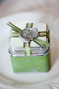 Small metal boxes wrapped with green scrapbook paper stamped with silver ink in a filigree pattern. Matching ribbon decorates the lid with a wax seal in the couple's monogram. The boxes were filled with wildflower seed mix to match the garden theme. Photo by Bradley Images.