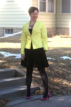 Yellow blazer, black tank and skirt, patterned tights, pink necklace and pumps