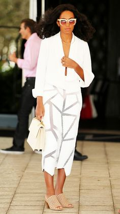 Solange Knowles wears a white top, sheer paneled white skirt, and gold and nude accessories