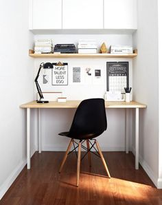 Small scandinavian Home Office with white walls Dark hardwood floors and a…