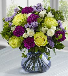"The FTD® Picture Perfect Bouquet by Better Homes and Gardens® - VASE INCLUDED -This bouquet includes the following: green roses, white spray roses, purple carnations, lavender carnations, lavender statice, and an assortment of lush greens with a purple glass vase. BETTER bouquet includes 17 stems with vase. Approximately 13""H x 12""W."