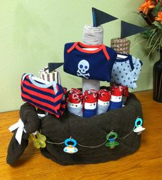 Finished pirate ship diaper cake. Consists of 90 diapers, 3 receiving blankets, 3 spoons, 3 onesies, 3 pacifiers, 6 washcloths, 1 knit baby blanket, 1 bottle brush, 1 9oz bottle, 1 4oz bottle, and 1 teething ring. Custom Order made 9/26/2013.