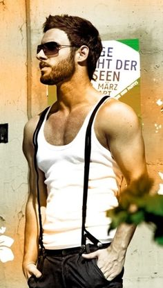 Facial hair and shades. Tank top and suspenders.