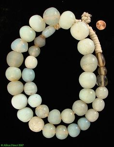 "Trade Beads |  Opalescent Moon Beads | Made in Europe for the Africa trade in the mid 1800s. | The origin and period of these rare opalescent beads are uncertain. They have been attributed to Venice, Bohemia, Germany and the Netherlands, where they are called ""18th century Amsterdams."" The beads can be found on the sample cards of a prominent London merchant named Moses Lewin Levin that are dated 1851-1869.  