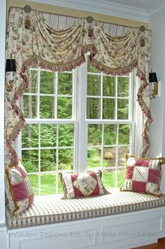 Custom window treatments frame the view of this cozy window seat