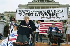 Justin Dart on a platform with a sign behind him: Injustice anywhere is a threat to justice everywhere. - Martin Luther King