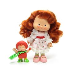 This vintage Strawberry Shortcake doll is the Berrykin version of Strawberry Shortcake. She comes with her little Strawberrykin critter. She wears a pink and red dress with lace trim, striped pastel t