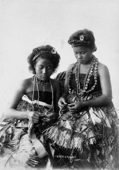 Unidentified Samoan women wearing traditional clothing, making wreaths. Photograph taken by Thomas Andrew, circa 1890s.  Inscriptions: Inscribed - Photographer's title on negative -bottom centre: Wreath making Sam. National Libary of New Zealand.