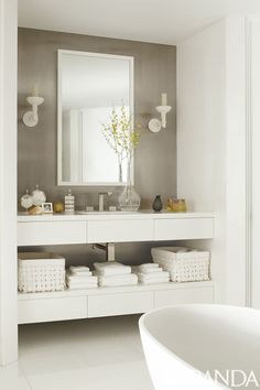 White sconces and linens pop against the gray wall in this Boston bathroom. The tub is by MTI Baths, the sink fittings are by Gessi and the sconces are by Jasper.   Image originally appeared in the January 2014 issue of Veranda.   INTERIOR DESIGN BY RICHARD HALLBERG
