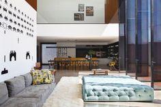 """Além do estar, com sua parede solteira decorada por adesivos dos """"Space Invaders"""", famosos """"personagens"""" do jogo homônimo para o console Atari dos anos 1980, desse ângulo, vê-se a sala de jantar e a cozinha ao fundo e, acima, a parede que delimita os dormitórios. Em primeiro plano, o sofá MiCasa foi combinado ao pufe Miniloft. A LA House foi projetada pelo Studio Guilherme Torres e fica em Londrina (PR)"""