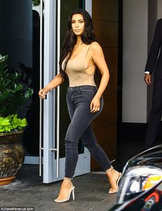 All her: She invariably teams the revealing tops with a pair of trousers - in this case a skintight pair of jeans