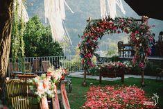 Cerimônia ao ar livre com decoração em tons de marsala, pêssego e verde, com direito a um arco de flores no altar e pétalas como tapete.