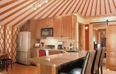 30' Yurts - Pacific Yurts  Nice kitchen layout with a bedroom and sliding barn door