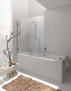 petite salle de bains blanche aménagée avec une baignoire douche et un tapis shaggy marron clair