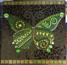 Butterfly in glass tiles and beads, grouted in black.