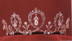 Swedish Crown Jewels: the Connaught Tiara has 5 upright loops of forget-me-not wreaths with a diamond pendant suspended in each. Between the loops, upside down bows support single diamond uprights.  Made by E. Wolff  Co., it was a wedding gift to Princess Margaret of Connaught from her parents, the Duke and Duchess of Connaught, when she married the future King Gustaf VI Adolf of Sweden in 1905.